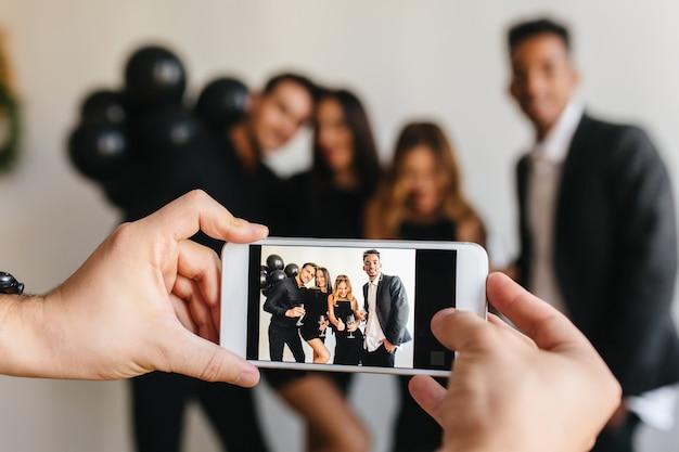 Mann in der armbanduhr, die weißes smartphone hält und foto von freunden macht, die spaß auf party haben