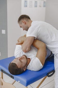 Mann in der arztpraxis. der physiotherapeut rehabilitiert den rücken.