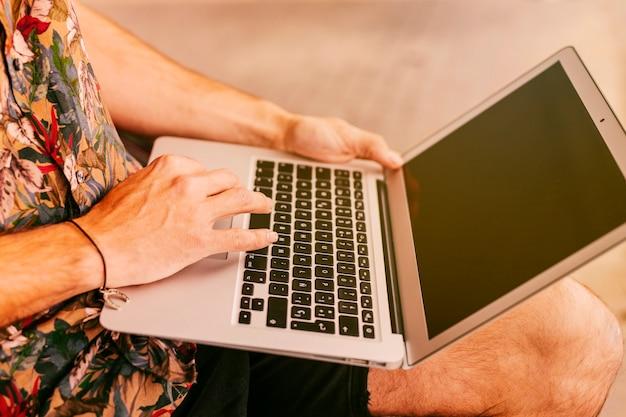Mann in der beiläufigen kleidung, die an laptop arbeitet