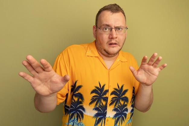 Mann in der brille, die das orangefarbene hemd trägt, besorgt mit den armen, die verteidigungsgestik machen, die über grüner wand steht