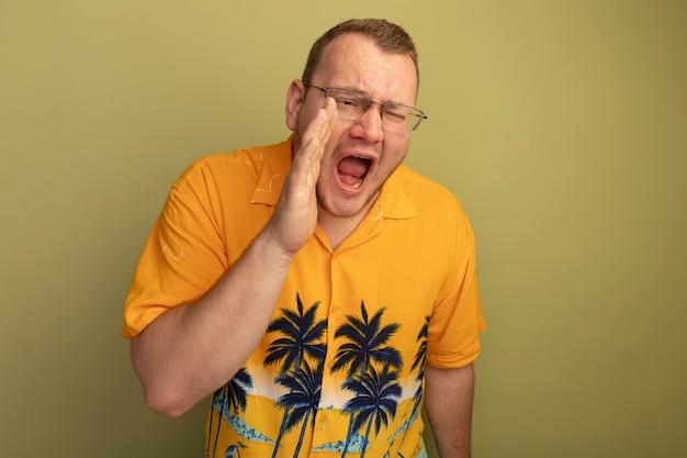 Mann in der brille, die das orangefarbene hemd trägt, das mit der hand nahe dem mund schreit oder ruft, der über der hellen wand steht