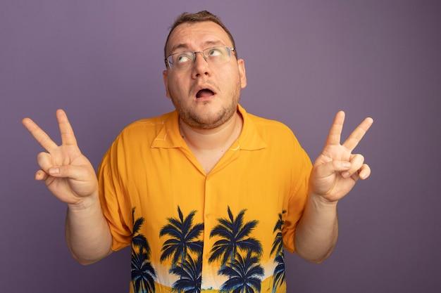 Mann in der brille, die das orangefarbene hemd trägt, das oben zeigt, das verwirrtes v-zeichen zeigt, das über lila wand steht