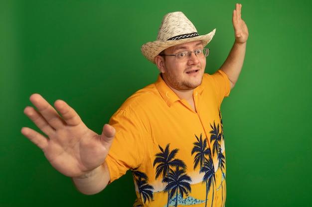 Mann in der brille, die orange hemd und sommerhut mit glücklichem gesicht trägt, das arme zu den seiten spreizt, die über grüner wand stehen