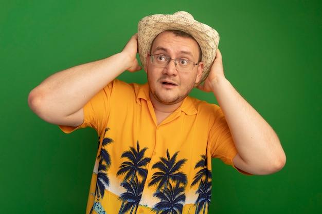 Mann in der brille, die orange hemd und sommerhut trägt, die beiseite schauen überrascht, seinen hut berührend, der über grüner wand steht