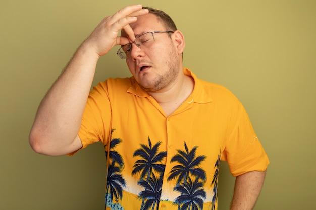 Mann in der brille, die oranges hemd trägt, das seine nase zwischen geschlossenen augen berührt müde und gelangweilt, über grüner wand stehend