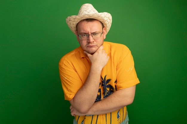 Mann in der brille, die oranges hemd und sommerhut mit hand auf seinem kinn trägt und mit ernstem gesicht über grüner wand steht