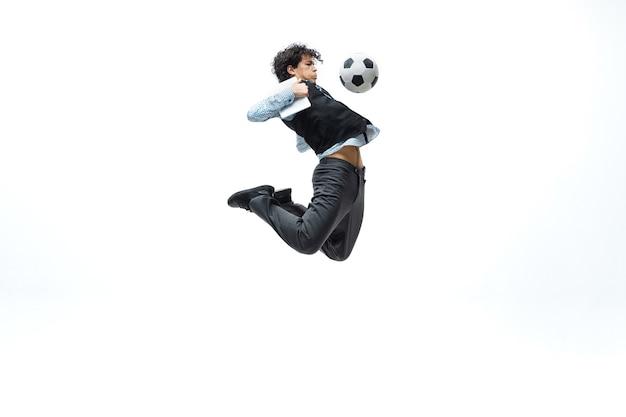 Mann in der bürokleidung, die fußball oder fußball mit ball auf weiß spielt.