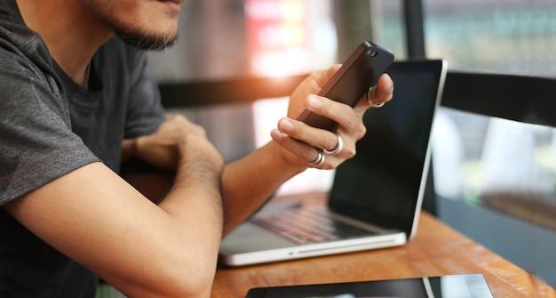 Mann in der freizeitkleidung mit mobilem smartphone in der hand und laptop auf tabelle