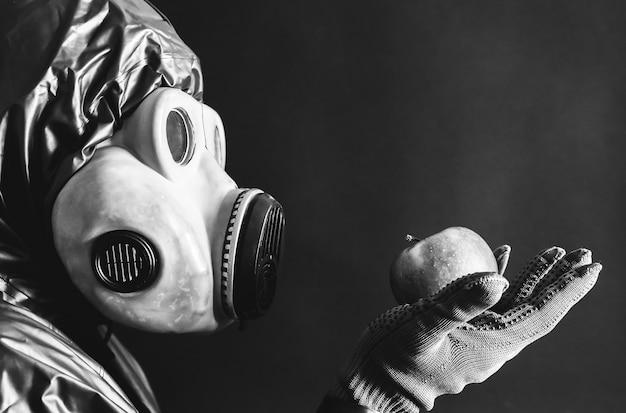 Mann in der gasmaske, die apfel hält strahlungseinfluss. umweltverschmutzung. tschernobyl-konzept. gefährliche atomkraft. ökologisches desaster.