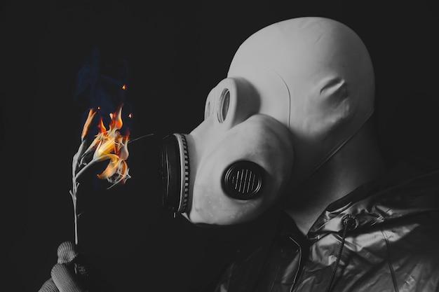 Mann in der gasmaske, die blume in brand hält. strahlungseinfluss. umweltverschmutzung. tschernobyl-konzept. gefährliche atomkraft. ökologisches desaster.