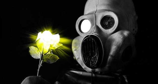 Mann in der gasmaske, die gelbe leuchtende blume hält strahlungseinfluss. umweltverschmutzung. tschernobyl-konzept. gefährliche atomkraft. ökologisches desaster.