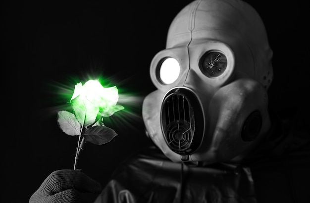 Mann in der gasmaske, die grüne leuchtende blume hält strahlungseinfluss. umweltverschmutzung. tschernobyl-konzept. gefährliche atomkraft. ökologisches desaster.
