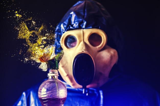 Mann in der gasmaske, die plastikflasche mit blume hält, die in stücke fällt. strahlungseinfluss. umweltverschmutzung. tschernobyl-konzept. gefährliche atomkraft. ökologisches desaster.
