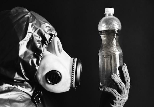 Mann in der gasmaske, die plastikflasche mit schmutzigem wasser hält strahlungseinfluss. umweltverschmutzung. tschernobyl-konzept. gefährliche atomkraft. ökologisches desaster.