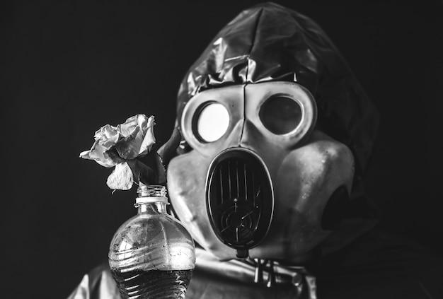 Mann in der gasmaske, die plastikflasche mit schmutzigem wasser und blume hält strahlungseinfluss. umweltverschmutzung. tschernobyl-konzept. gefährliche atomkraft. ökologisches desaster.