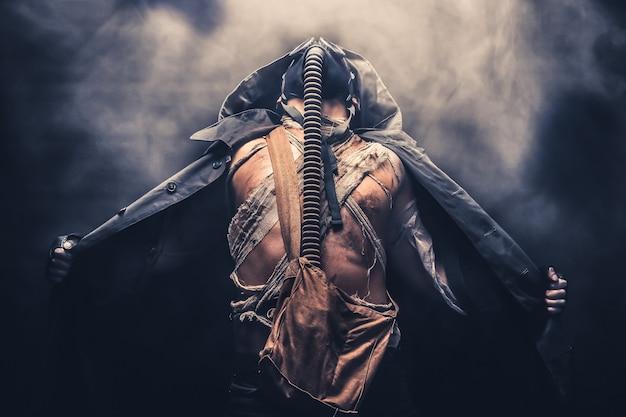 Mann in der gasmaske in der haube, umgeben von rauch