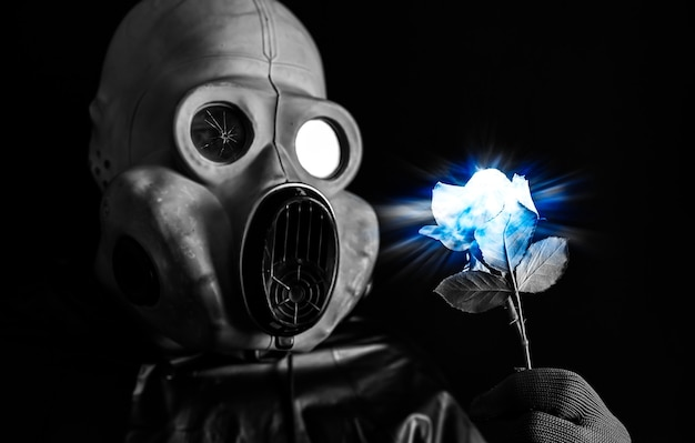 Mann in der gasmaske mit blau leuchtender blume. strahlungseinfluss. umweltverschmutzung. tschernobyl-konzept. gefährliche atomkraft. ökologisches desaster.