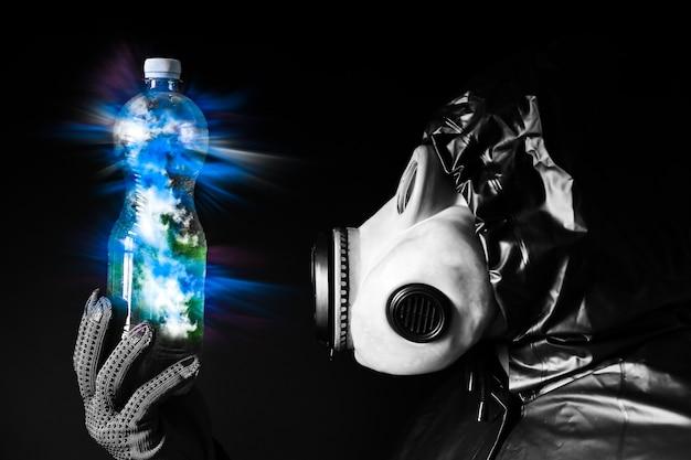 Mann in der gasmaske mit plastikflasche. blau leuchtendes licht. strahlungseinfluss. umweltverschmutzung. tschernobyl-konzept. gefährliche atomkraft. ökologisches desaster.