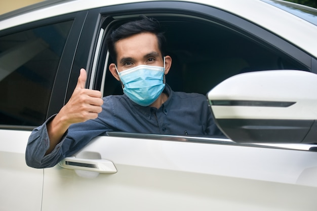 Mann in der gesichtsmaske, die in einem auto sitzt