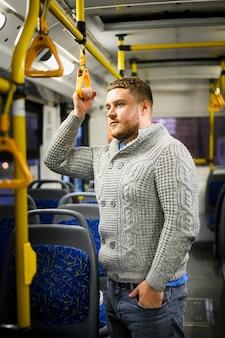 Mann in der grauen bluse und in den jeans, die mit dem bus reisen