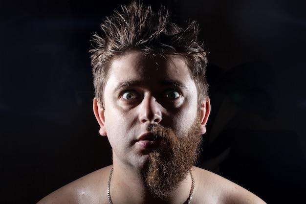 Mann in der hälfte rasiert mit weit geöffneten augen und schaut in die kamera an einer schwarzen wand Premium Fotos