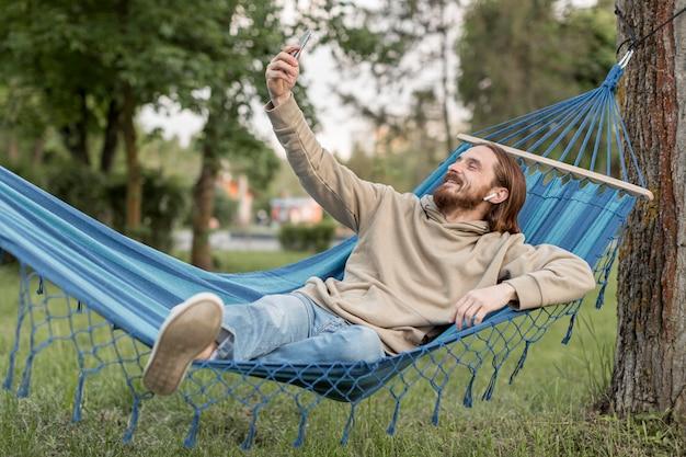 Mann in der hängematte, die selfies mit smartphone nimmt
