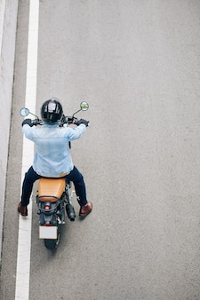 Mann in der jeansjacke, die auf motorrad auf autobahn fährt, ansicht von oben