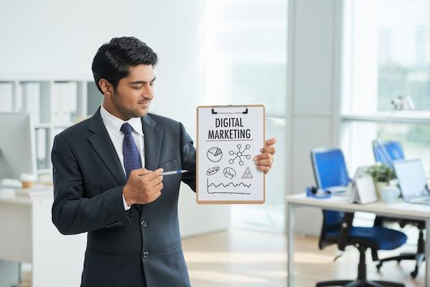 Mann in der klage, die im büro mit klemmbrett steht und auf plakat mit wörtern zeigt