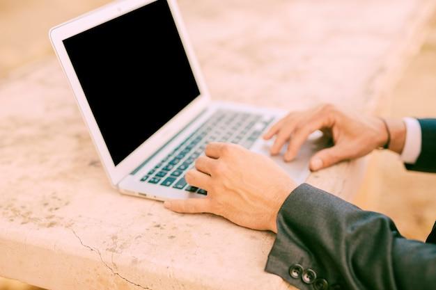 Mann in der klage, die mit kleinem laptop arbeitet