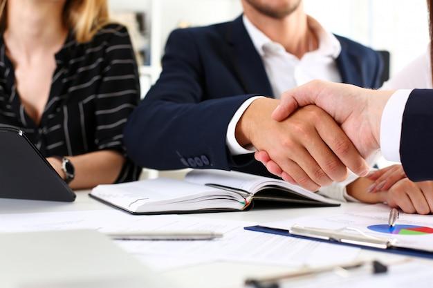 Mann in der klage rütteln hand als hallo in der büronahaufnahme