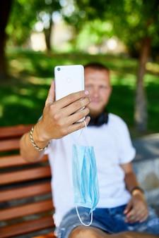 Mann in der medizinischen maske, die auf der bank im park sitzt, nehmen selfie per handy