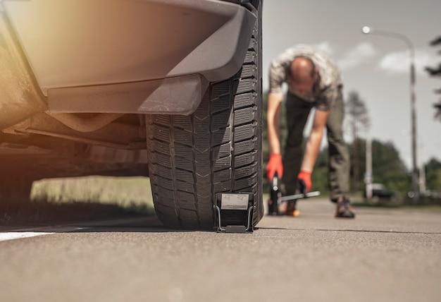 Mann in der nähe von autoreifen mit auto-wagenheber-werkzeug niedrige winkelsicht