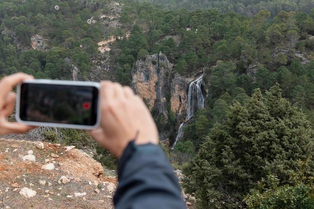 Mann in der natur, die fotos mit handy macht