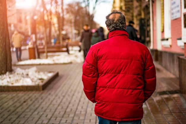 Mann in der roten jacke allein gehend auf die straße. rückansicht. mann über 50 jahre alt.
