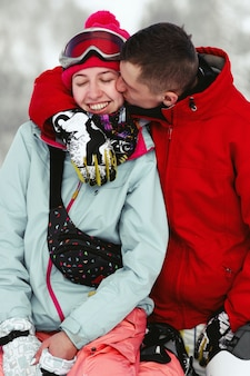 Mann in der roten skijacke küsst die backe der frau, während sie auf geschneitem hügel sitzen
