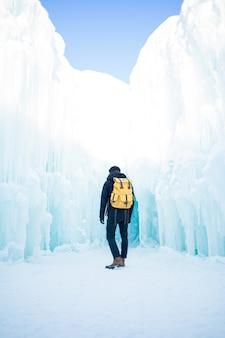 Mann in der schwarzen jacke und in den blauen jeans, die auf schneebedecktem boden stehen