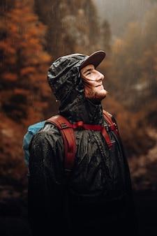 Mann in der schwarzen und roten jacke, die schwarzen hut trägt