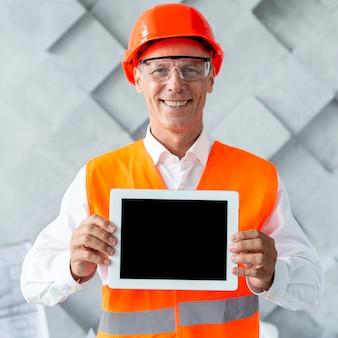 Mann in der sicherheitsausrüstung, die ein tablettenmodell zeigt