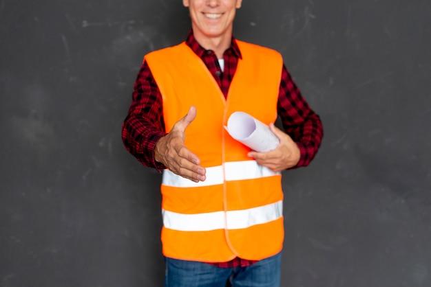 Mann in der sicherheitsausrüstung, die einen handshake gibt