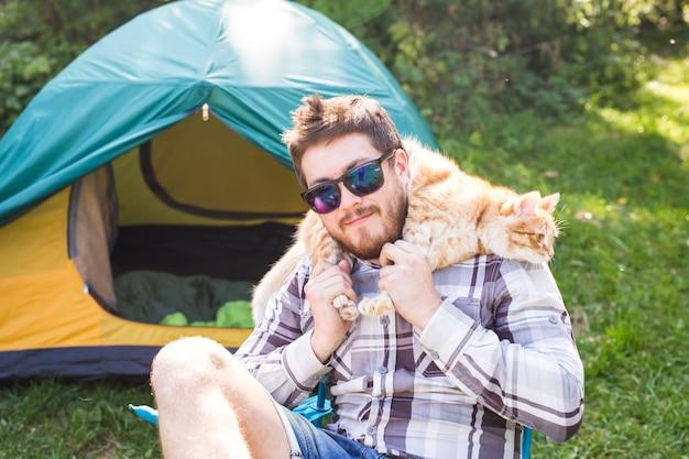 Mann in der sonnenbrille, die katze auf schultern hält