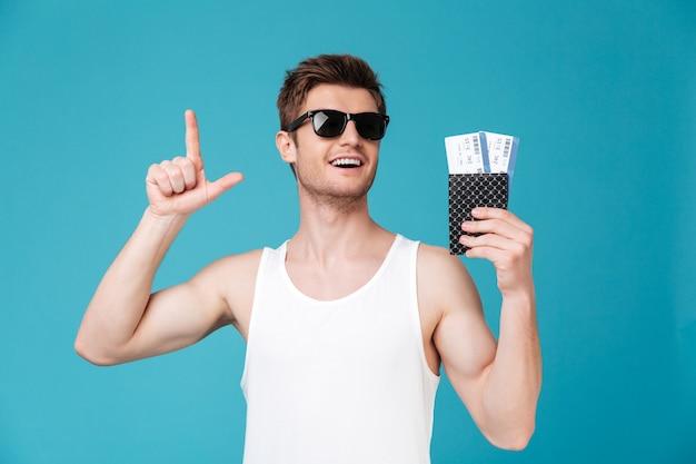 Mann in der sonnenbrille, die pasport mit tickets hält