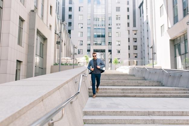 Mann in der sonnenbrille läuft auf betontreppe