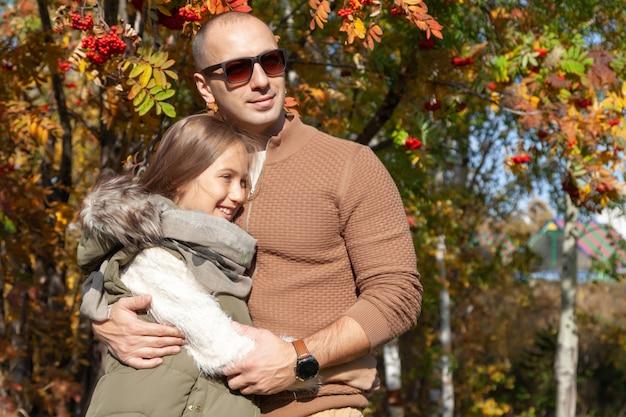 Mann in der sonnenbrille umarmt schöne tochter auf hintergrund von bunten herbstbäumen