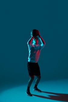 Mann in der sportbekleidung, die basketball mit kühlen lichtern spielt