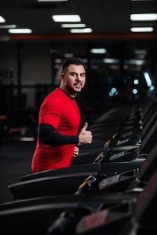 Mann in der sportkleidung, die auf tretmühle an der turnhalle in der roten kleidung läuft