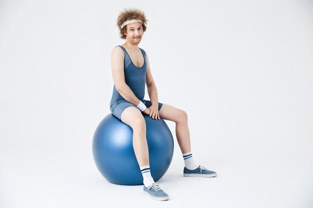 Mann in der sportkleidung, die auf übungsball sitzt und gesichter macht