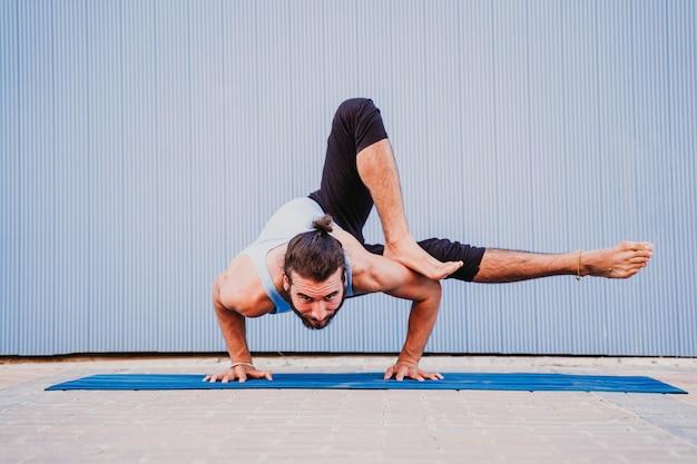 Mann in der stadt, die yogasport übt