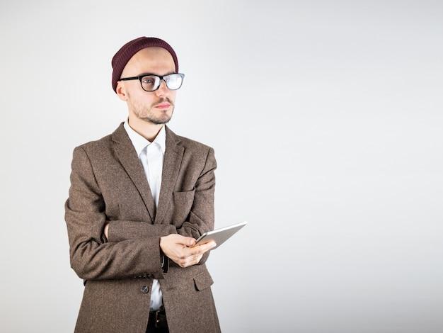 Mann in der tweedjacke mit einem tablet-computer. männliche geschäftsperson in der hippie-artkleidung benutzt technologie, atelieraufnahme im weißen hintergrund