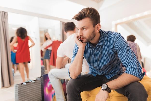 Mann in der umkleidekabine wartet auf seine freundin