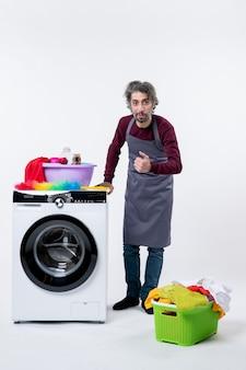 Mann in der vorderansicht in schürze, der hand auf einen wäschekorb der waschmaschine auf der weißen wand des bodens legt